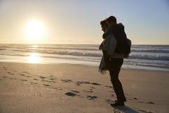 Silueta del padre Giving Son Piggyback en la playa del invierno imagen de archivo