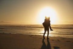 Silueta del padre Giving Son Piggyback en la playa del invierno fotos de archivo libres de regalías