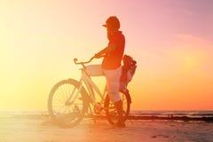 Silueta del padre y del bebé biking en la puesta del sol Imagenes de archivo
