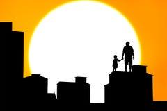 Silueta del padre y del hijo que se colocan en el edificio Imagenes de archivo