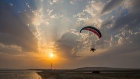 Silueta del Paragliding en la puesta del sol de la playa Imagenes de archivo