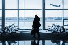 Silueta del pasajero que espera el vuelo en aeropuerto fotos de archivo