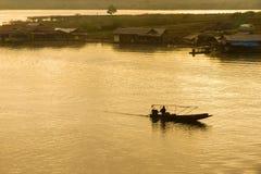 Silueta del paseo del barco del hombre del canotaje en el río en la puesta del sol en el Sa imagen de archivo