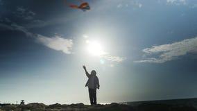 Silueta del pequeño niño que sostiene la cometa del vuelo en fondo del mar en verano almacen de video