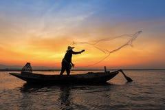 Silueta del pescador asiático en el barco de madera en la acción Fotos de archivo