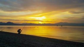 Silueta del pescador contra una puesta del sol dramática almacen de metraje de vídeo