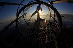 Silueta del pescador del intha contra el cielo de la puesta del sol imagenes de archivo