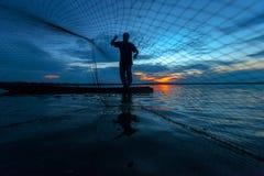 Silueta del pescador en el lago en la acción Fotografía de archivo