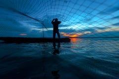 Silueta del pescador en el lago en la acción Fotos de archivo libres de regalías