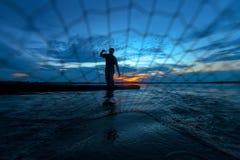 Silueta del pescador en el lago en la acción Fotos de archivo