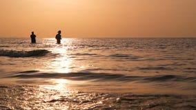 Silueta del pescador en la acción al hacer girar el tiempo de la puesta del sol Empleo y manera asiáticos tradicionales de obtene almacen de video