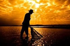 Silueta del pescador en la puesta del sol Imagen de archivo libre de regalías