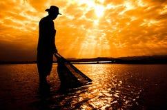 Silueta del pescador en la puesta del sol Fotografía de archivo libre de regalías