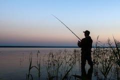 Silueta del pescador en la puesta del sol Imagenes de archivo