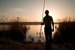 Silueta del pescador en la puesta del sol cerca del lago Imagenes de archivo