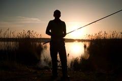 Silueta del pescador en la puesta del sol cerca del lago Foto de archivo