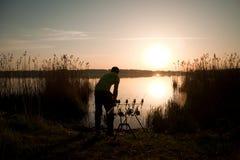 Silueta del pescador en la puesta del sol cerca del lago Fotografía de archivo