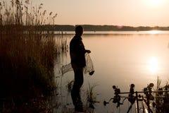 Silueta del pescador en la puesta del sol cerca del lago Fotos de archivo libres de regalías