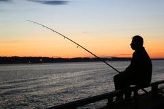 Silueta del pescador en la puesta del sol cerca del puente de Verrazano en el puerto de Nueva York Foto de archivo