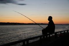 Silueta del pescador en la puesta del sol cerca del puente de Verrazano en el puerto de Nueva York Foto de archivo libre de regalías