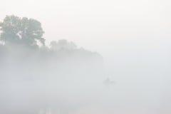 Silueta del pescador en un río en la mañana brumosa Fotografía de archivo