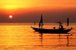 Silueta del pescador y de los barcos que flotan en la orilla de mar Fotografía de archivo libre de regalías