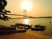 Silueta del pescador y de sus barcos durante puesta del sol Fotos de archivo libres de regalías