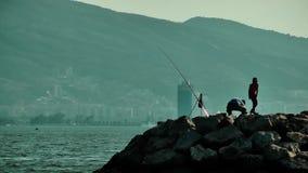 Silueta del pescador y del niño en las rocas metrajes