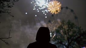 Silueta del primer de los fuegos artificiales de observación del hombre solo en la celebración del Año Nuevo al aire libre metrajes