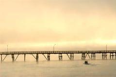 Silueta del puente de madera en la niebla. Foto de archivo