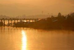 Silueta del puente de madera y de la aldea de lunes. Foto de archivo