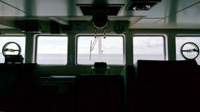 Silueta del puente del ` s de la nave con el mar y del cielo delante de las ventanas fotografía de archivo