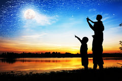 Silueta del punto de la mano del uso del padre su mirada del hijo en la Luna Llena Imagen de archivo libre de regalías