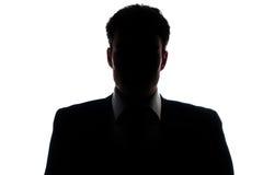 Silueta del hombre de negocios que lleva un juego Fotos de archivo libres de regalías