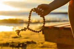 Silueta del rosario en manos femeninas en un fondo de la puesta del sol, Fotografía de archivo libre de regalías