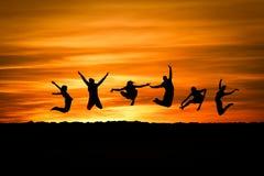Silueta del salto de los amigos Foto de archivo libre de regalías