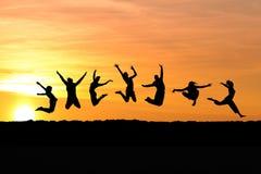 Silueta del salto de los amigos Imagen de archivo