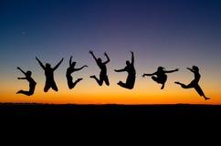 Silueta del salto de los amigos Foto de archivo