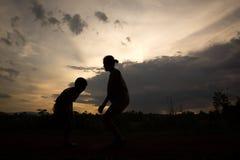 Silueta del salto del muchacho y de la muchacha Fotografía de archivo