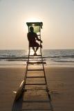 Silueta del salvavidas que pasa por alto la playa tropical Imagen de archivo