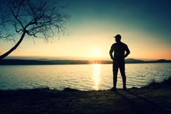 Silueta del soporte del hombre joven en la playa en la puesta del sol Sombra del hombre activo Fotos de archivo libres de regalías