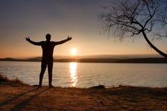 Silueta del soporte del hombre joven en la playa en la puesta del sol Sombra del hombre activo Imágenes de archivo libres de regalías
