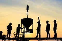 Silueta del soporte del trabajador de construcción en columna del hormigón colado del marco del andamio en emplazamiento de la ob Foto de archivo libre de regalías