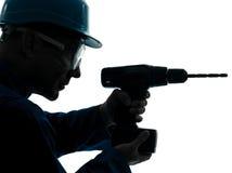 Silueta del taladro de la tenencia del trabajador de construcción del hombre foto de archivo libre de regalías