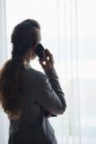 Silueta del teléfono celular de la mujer de negocios que habla Imagen de archivo