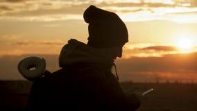 Silueta del teléfono turístico joven del uso de la mujer con el fondo dramático del cielo de la puesta del sol Conectado siempre, metrajes