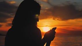 Silueta del teléfono turístico joven del uso de la mujer durante puesta del sol en playa del océano Conectado siempre, el concept almacen de metraje de vídeo