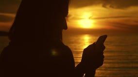 Silueta del teléfono turístico joven del uso de la mujer durante puesta del sol en playa del océano Conectado siempre, el concept metrajes