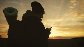 Silueta del tel?fono tur?stico joven del uso de la mujer con el fondo dram?tico del cielo de la puesta del sol Conectado siempre, almacen de video