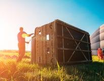 Silueta del trabajador cerca de la cesta de globo del aire caliente que la prepara para el vuelo en la luz de la puesta del sol fotografía de archivo
